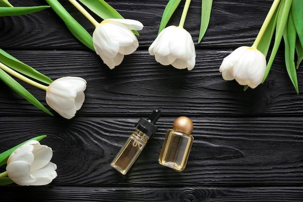 木製のテーブルに香水と花との構成