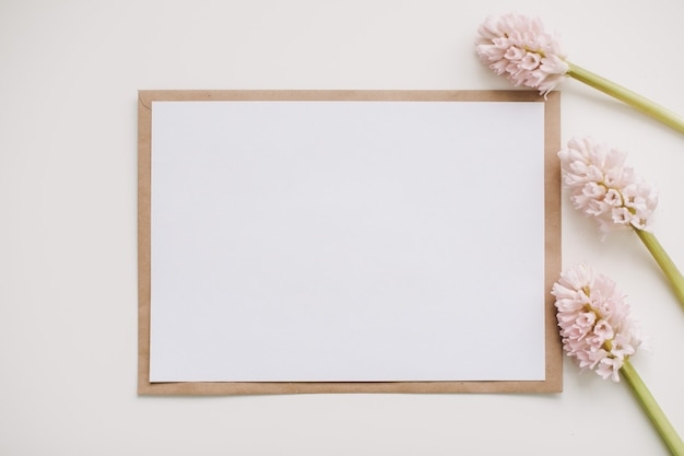Composition with pink flowers and blank paper card, mockup, invitations.