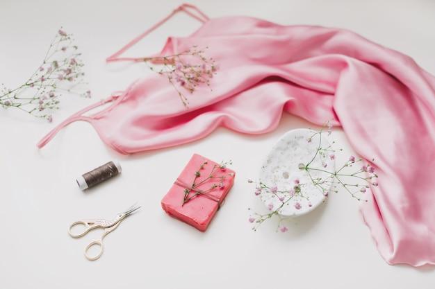 공예 종이와 실과 흰색 평면에 가위에 분홍색 실크 직물 선물 구성