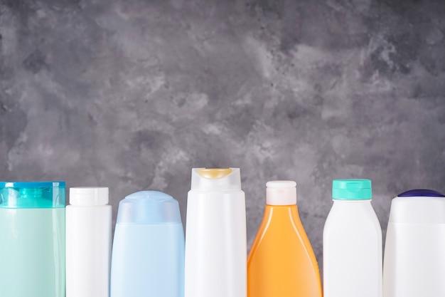 Композиция с пластиковыми бутылками по уходу за телом и косметическими продуктами на сером фоне. место для текста.
