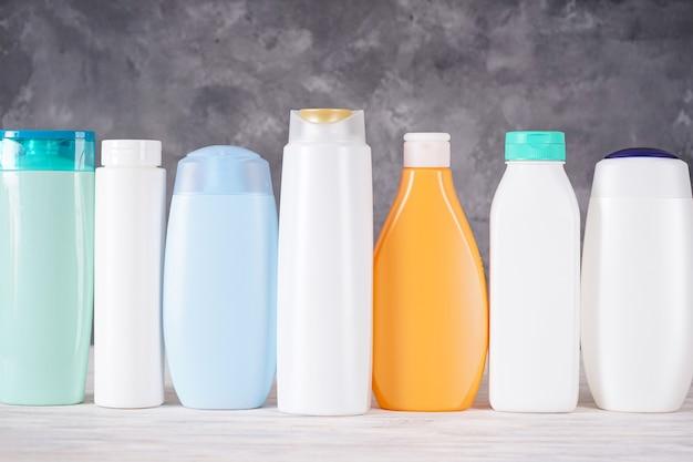 Композиция с пластиковыми бутылками косметики и ухода за телом на сером фоне.