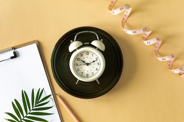 色付きの背景にプレート、目覚まし時計、巻尺で構成。ダイエットのコンセプトと減量計画、コピースペース