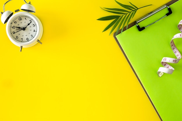 Композиция с тарелкой, будильником и рулеткой на цветном фоне. концепция диеты и план потери веса, копия пространства