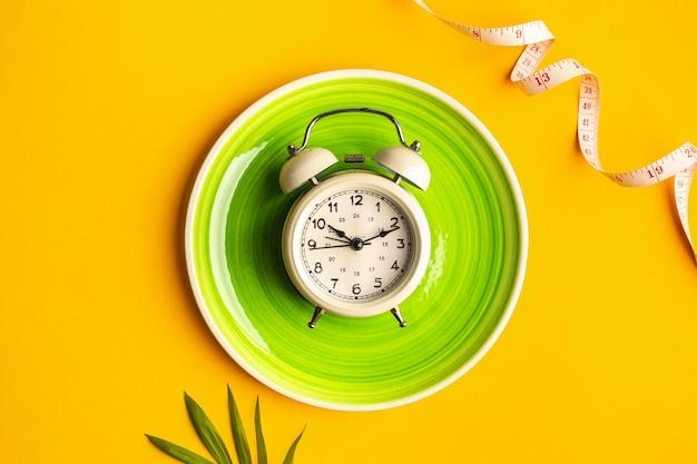 접시, 알람 시계와 컬러 배경에 측정 테이프 구성. 다이어트 개념 및 체중 감량 계획, 복사 공간
