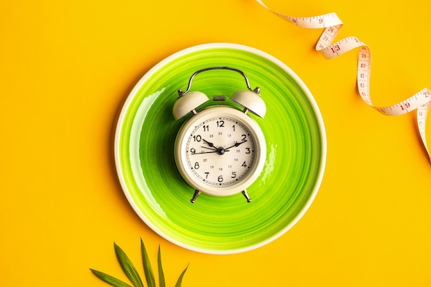 Composition with plate, alarm clock and measuring tape on a colored background. diet concept and weight loss plan, copy space