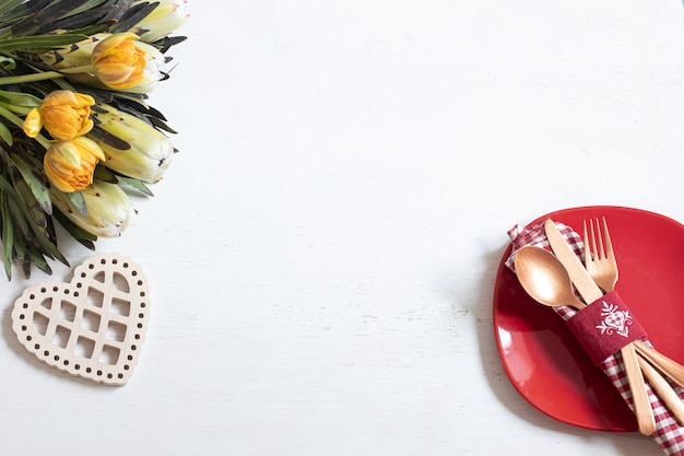 Composition with a plate and cutlery for a romantic dinner and decorative elements valentine's day top view. dating concept.