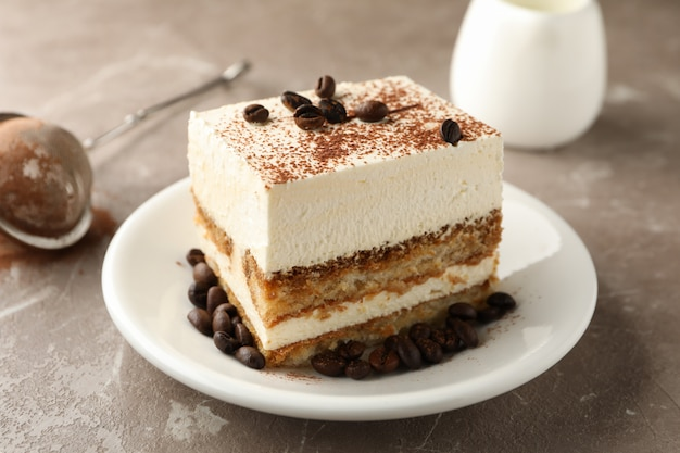 明るい茶色の背景にティラミスのプレートと組成。おいしいデザート
