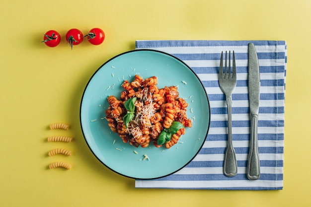 Composition with plate of pasta tomato basil napkin and cutlery on a yellow background creative flat lay