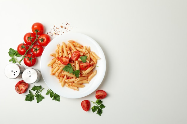 Composition with plate of tasty pasta and ingredients for cooking on white wall