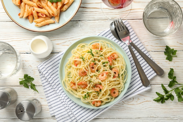 Composition with plate of tasty pasta with shrimps on wooden wall