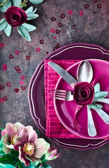 Composition with plates and crockery decorated with magenta paper roses