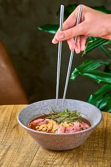 나무 배경에 회색 접시에 쇠고기와 라면 수프 구성