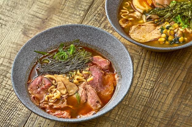 나무 배경에 회색 접시에 닭고기와 쇠고기를 곁들인 라면 수프 구성