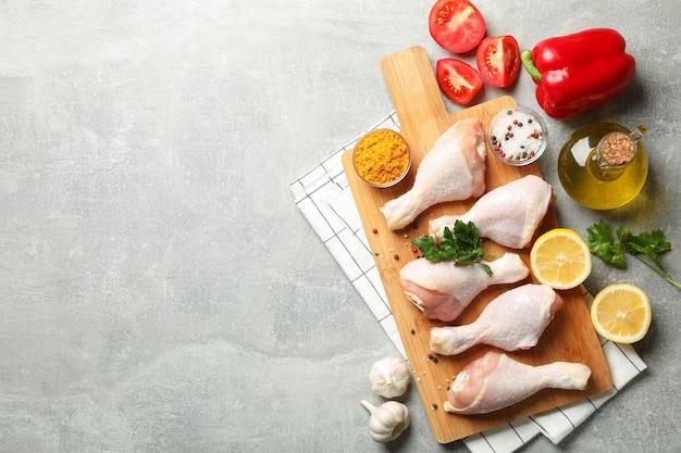 Композиция с сырым куриным мясом на сером пространстве, вид сверху