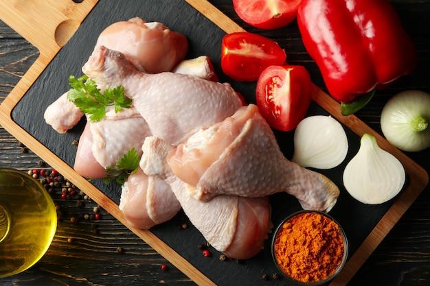 Композиция с сырым куриным мясом на деревянном пространстве, вид сверху