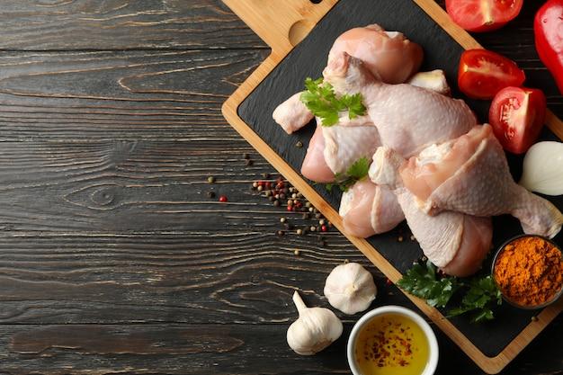 Композиция с сырым куриным мясом на деревянном, вид сверху