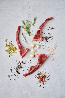 Composition with raw doe ribs with spice and herb over concrete background