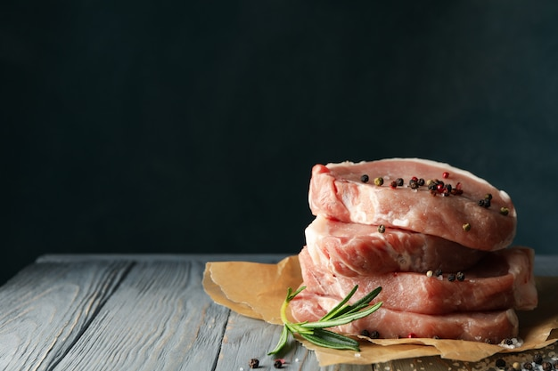 나무 테이블에 스테이크와 향신료에 대 한 생고기 구성