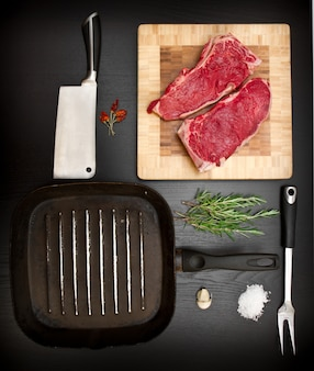 Composition with raw rib and kitchen tools on black wood