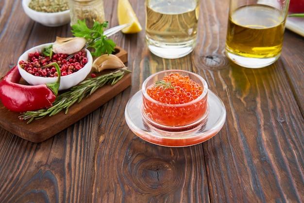 나무 테이블에 유리 항아리에 빨간 캐 비어와 요리 재료로 구성