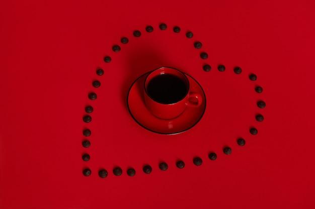テキスト用のスペースがある赤い表面にマルチカラーのチョコレートの丸薬が並んでいるハートの形の内側の受け皿にコーヒーとコーヒーを入れた赤いカップで構成