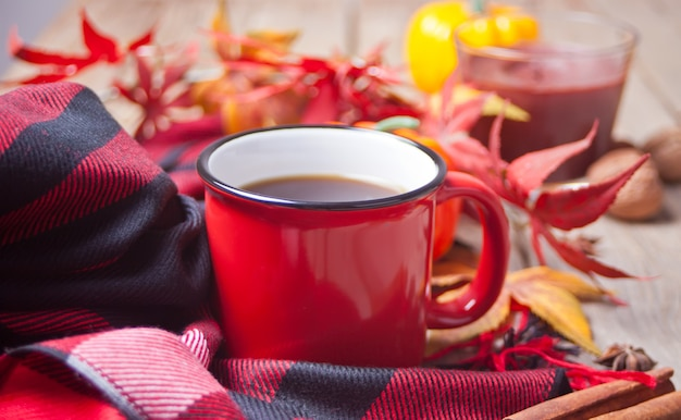 Composition with red mug with coffee, autumn leaves and small pumpkins