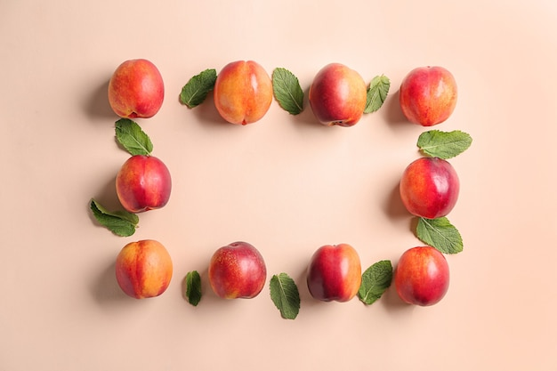 Composition with ripe peaches on color background, top view