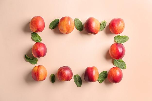 Композиция со спелыми персиками на цветном фоне, вид сверху