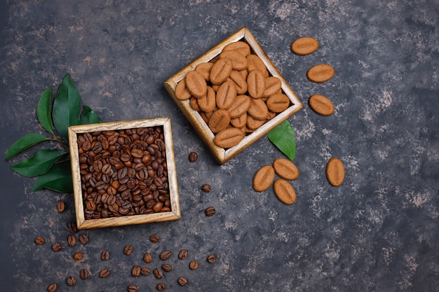 Composition with roasted coffee beans and coffee bean shaped cookies on dark brown surface