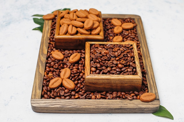 Composition with roasted coffee beans and coffee bean shaped cookies on light surface