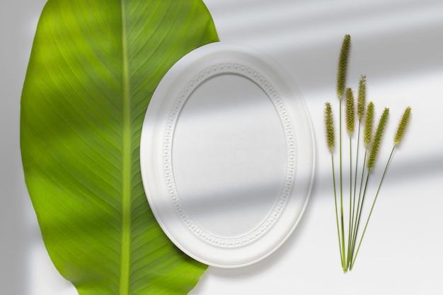 Композиция с круглой овальной белой пустой деревянной рамой, лежащей на зеленом листе с полевыми растениями