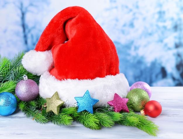 明るい背景にサンタクロースの赤い帽子とクリスマスの装飾との構成