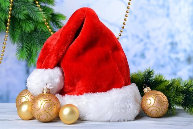 Композиция с красной шляпой санта-клауса и рождественскими украшениями на светлой стене
