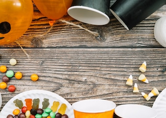 Composition with scattered paper cups and sweets on wooden table