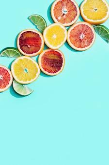 Композиция из кусочков цитрусовых, грейпфрута, красного апельсина, лимона, лайма на бирюзе. летняя еда