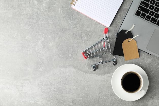 작은 쇼핑 카트, 노트북 및 커피 복사 공간 구성
