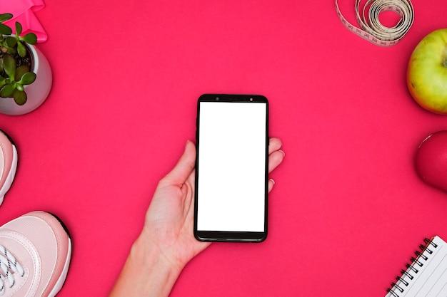 Композиция с смартфона и спортивного инвентаря. кроссовки, рулетка, глюкометр на розовом