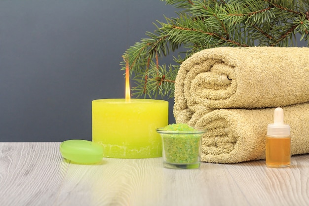 Composition with a soft terry towel, a bottle with aromatic oil, soap, a bowl with sea salt, a burning candle and a fir tree branch on the gray background