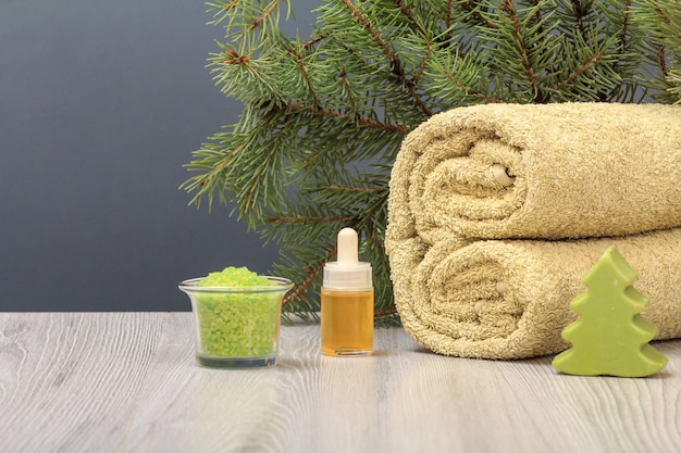 Composition with a soft terry towel, soap, a bottle with aromatic oil, a bowl with sea salt and a fir tree branch on the gray background