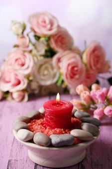 明るい表面に、色の木製テーブルにスパストーン、キャンドル、花を使った構図
