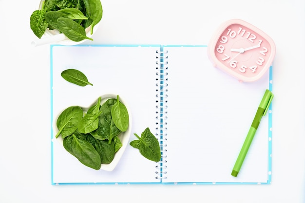 Composition with  spinach, measuring tape, blank paper notebook and pink alarm clock on white table.  diet concept, copy space