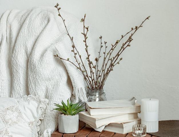 部屋のインテリアに春の枝、本、キャンドルを使ったコンポジション。