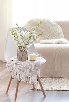 居心地の良いリビングルームのインテリアに春の花のコンポジション。インテリアと快適さのコンセプト。