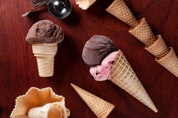 Composition with strawberry and chocolate ice cream in waffle cone on wooden background copy space top view