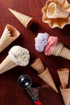 Composition with strawberry, grape and vanilla ice cream in waffle cone on wooden background. copy space. top view