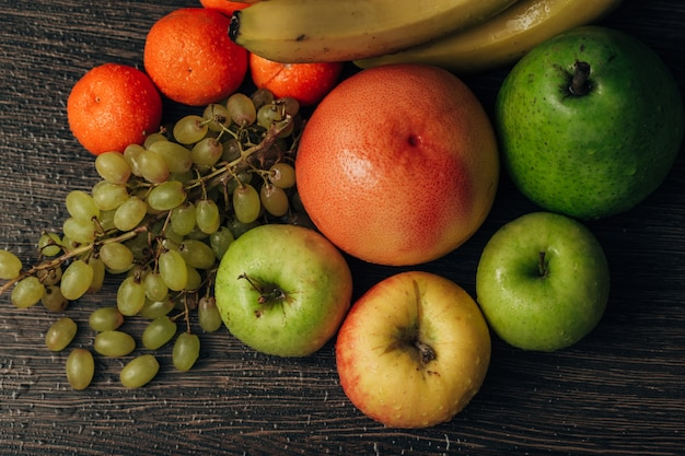 Composition with summer colorful fresh fruits on wooden brown background