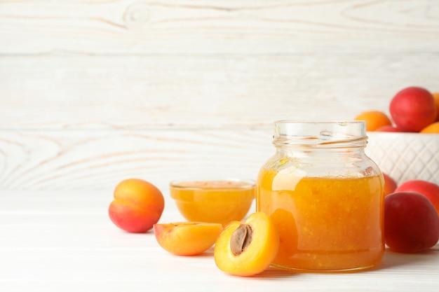 Композиция с вкусными абрикосами и вареньем на белом деревянном столе