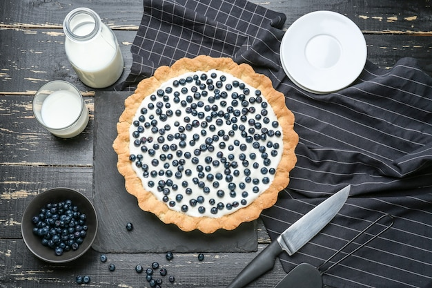 Composition with tasty bilberry pie on table