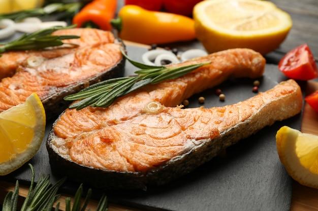 Композиция с вкусным жареным лососем на деревянном столе, крупным планом