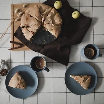 Композиция с вкусным домашним яблочным пирогом с корицей и яблоками на столе плоская планировка вид сверху